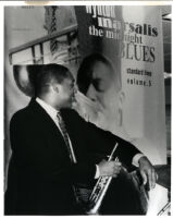 Wynton Marsalis posing in front of a poster of himself, 1986 [descriptive]