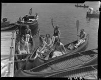 Women in canoes, men in motorboat, docked, Lake Arrowhead, 1929