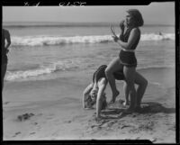 Young women at beach, performing back bend and applying makeup, Venice, 1930