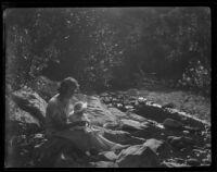 Woman and baby seated near stream, Santa Monica, circa 1922