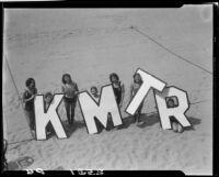 Young women on beach promoting radio station KMTR, Santa Monica, circa 1930