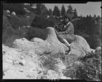 Mrs. Tom Carlisle seated on rock formation, Riverside County, [1920-1939?]