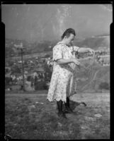 Woman standing on a hill and holding twine having to do with the Mary Skeele kidnapping case, 1933