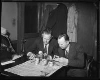 Officials working on the Mary Skeele kidnapping case at a desk with open cans of food, 1933