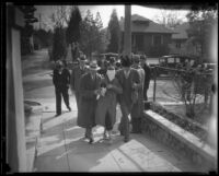 Kidnapping victim Mary Skeele walking blindfolded with a group of men [police detectives?], Los Angeles, 1933