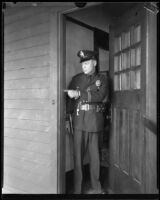 Police officer with the Mary Skeele kidnapping case pointing to a door frame, 1933