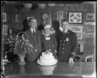 Fire chief Ralph Scott, Mrs. Adeline Scott, and O. [?] Edwards, with flowers and cake, 1929