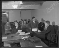 Edward S. Shattuck examining papers in a Superior Court chamber, between 1932-1939