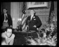 Joseph Shaw, personal secretary and brother of Los Angeles Mayor Frank Shaw, at desk with microphones, Los Angeles, 1933-1938