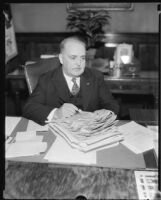 Los Angeles Mayor Frank Shaw at desk with papers, Los Angeles, 1933-1938