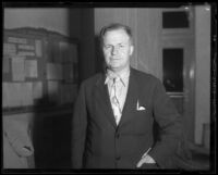 Man in jacket with rumpled collar and tie near bulletin board, [1933-1938?]