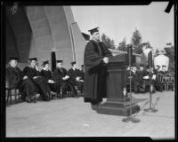 Robert G. Sproul, in cap and gown, speaking at UCLA graduation ceremony at Hollywood Bowl, Los Angeles, [1930s?]