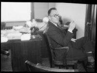 Lucas F. Smith seated near desk, 1934
