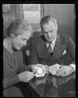 Los Angeles Park Commission president Mabel V. Socha and Deputy Chief of Police Homer Cross examining counterfeiting equipment, [Los Angeles], 1935
