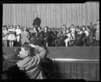 Composer John Philip Sousa onstage with school orchestra and school officials, Philharmonic Auditorium, Los Angeles, 1926