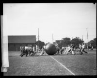 "Young men playing with large exercise ball at homecoming ""brawl,"" University of Southern California, Los Angeles, [1928?]"