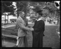 University of Southern California junior and senior class presidents sharing peace pipe and handshake at Ivy Day, Los Angeles, 1926