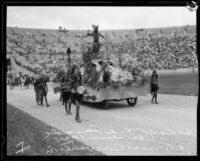 Belmont High School students in costume with float depicting California history, Shriners' parade, Los Angeles Memorial Coliseum, Los Angeles, 1925