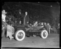 Actor Joe Murphy as Andy Gump, standing in car advertising movie, in Shriners' parade, Los Angeles Coliseum, Los Angeles, 1925