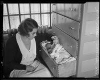 Los Angeles County Jail matron Vada Sullivan with baby sleeping in dresser drawer, 1933
