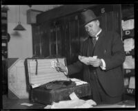 Detective or attorney examining contents of suitcase, possibly evidence in Fay Sudow murder case, [1920?]