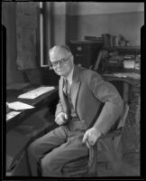 Elias Ransome Sutton seated at his desk, 1930