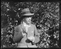 Crown Prince Gustav Adolf of Sweden tries an orange at an orchard, Riverside, 1926