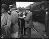 Crown Prince Gustav Adolf of Sweden signing a document for a man at a train station, Los Angeles, 1926