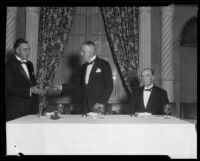 Realtor Clifford C.C. Tatum exchanging gavel with another man at real estate banquet, [1925-1930?]