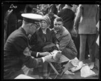 Woman wounded by the collapse of a Rose Parade grandstand receives first aid, Pasadena, 1926