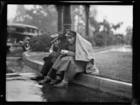 Two men seated on a streetside curb during the rainy Tournament of Roses Parade, Pasadena, 1934