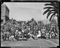 Rose Parade spectators next to building and train engine, Pasadena, 1930