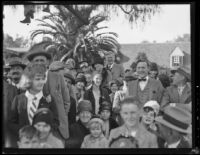 Close-up view of Rose Parade spectators on a residential street, Pasadena, 1930