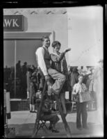 Couple on ladder on the sidewalk along the Rose Parade route, Pasadena, 1930