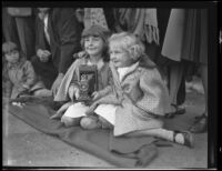 Two little girls with a camera seated on the Rose Parade route, Pasadena, 1930