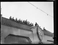 Rose Parade spectators on the roof of the Hupmobile dealer building on W. Colorado Blvd., Pasadena, 1930