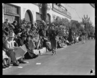Street vendor selling souvenir canes with toy footballs attached at the Tournament of Roses Parade, Pasadena, 1932