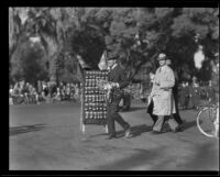 Street vendor with a football memento display walking along the route of the Tournament of Roses Parade, Pasadena, 1932