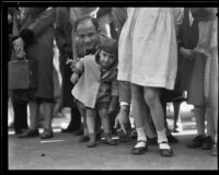 Father supporting toddler on the route of the Tournament of Roses Parade, Pasadena, 1932