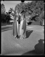 Two float riders costumed as fairies standing on a residential street at the start of the Tournament of Roses Parade route, Pasadena, 1933