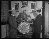 Mexican consul Joaquin Terrazas and Victor Manuel Pesqueira with plate and Mexican art, 1935