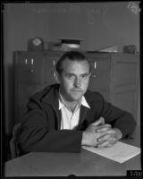 Jay Thomas sits at a desk, Los Angeles, 1934