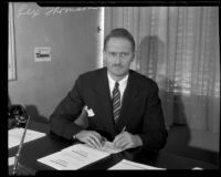 Rex Thomson sits at his desk, Los Angeles, 1934