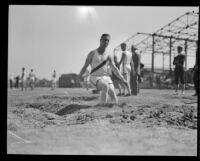 Athlete lands during the broad jump competition at the Pacific Fleet championship track meet, Long Beach, 1922