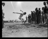 Sailor Flynn broad jumps during the Pacific Fleet's track championship meet, Long Beach, 1922