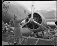 Barbara Douglas christens the TWA City of Los Angeles airplane before its maiden flight, Glendale, [1933]
