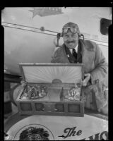 Col. Roscoe Turner holds gold sea chest intended for President Hoover, Los Angeles, 1932