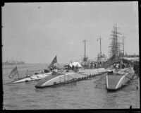Seen from behind, three Navy submarines on display to the public in the San Pedro harbor, 1932.