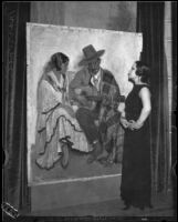 Artist Maroussia Valero standing before her painting of a seated Spanish couple with the man playing a guitar, circa 1932