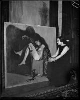 Artist Maroussia Valero seated before her painting of a sleeping nude, circa 1932